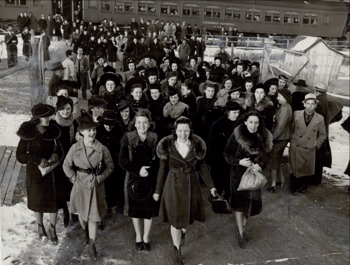 Crews of Canadian girls commute each day by special train to one of Canada's great war plants